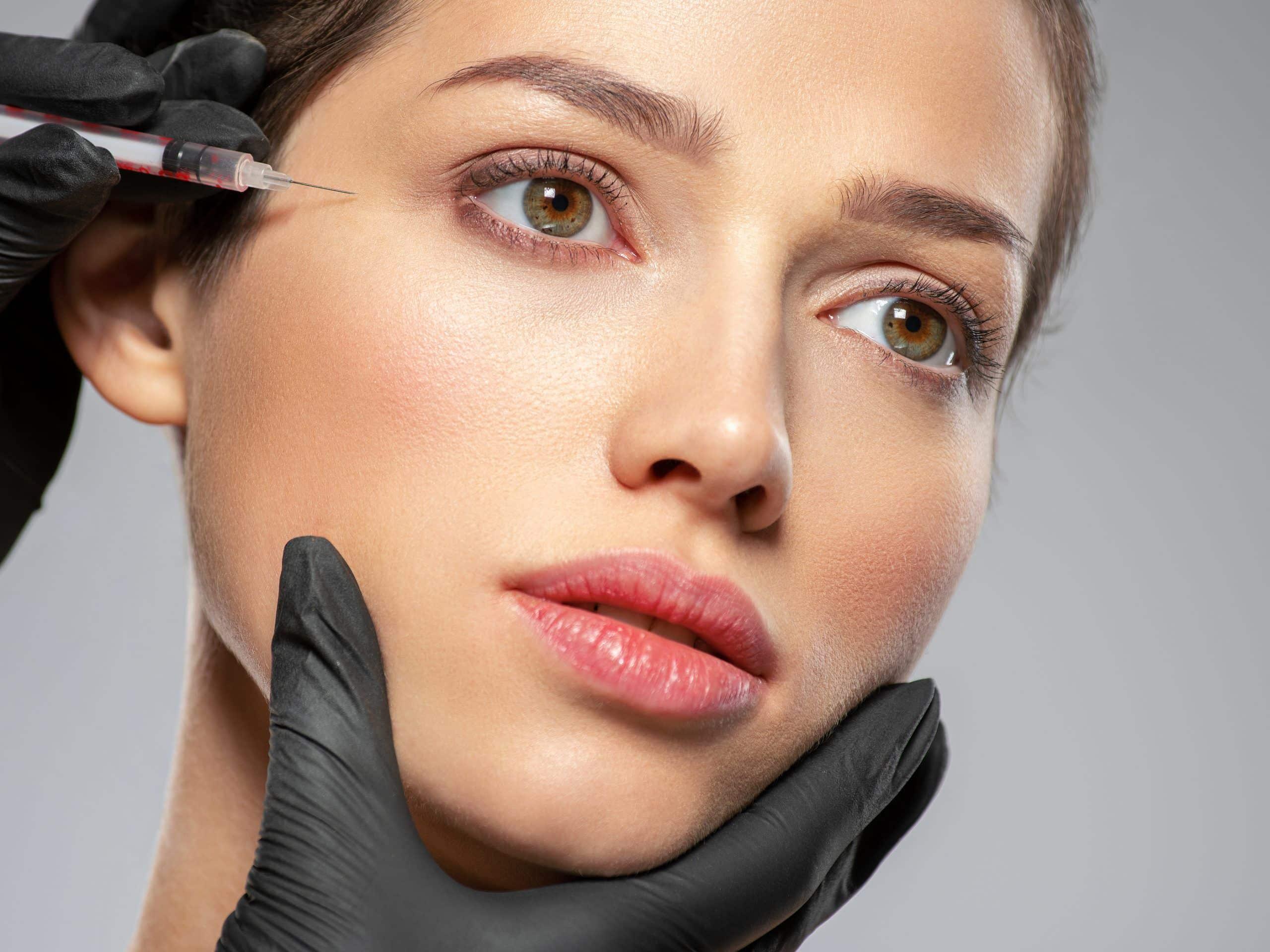 Mujer joven inyectando botox cerca de los ojos