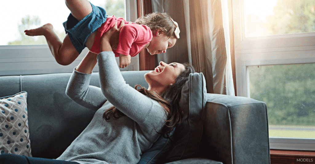 La madre sonríe mientras juega con su hijo